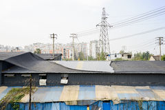 Dilapidated factory buildings before pylon and electrical poles Stock Photography