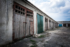 Dilapidated garage building. A dilapidated garage building against a cloudy evening sky Stock Photos