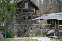 Dilapidated Gristmill Next to Shed. An abandoned gristmill with a dilapidated wheel along a path near a shed Stock Photo