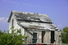Dilapidated House. Old, dilapidated wooden house with tin roof, uninhabited royalty free stock image