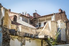 The dilapidated house. A dilapidated apartment building in the old districts of the city Stock Image