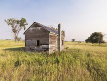 Dilapidated house in field. Dilapidated wooden house in rural field royalty free stock photos