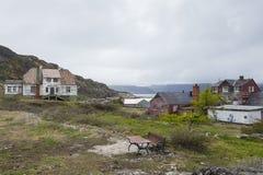 Dilapidated houten huizen met schilverf in dorp van de het spookmijnbouw van Groenland het verre stock foto