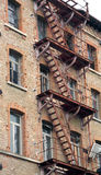 dilapidated industrial building with rusty fire escape with faci Stock Photos