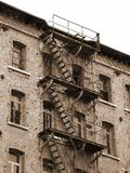 dilapidated industrial building with rusty fire escape with faci Royalty Free Stock Images