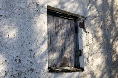 Boarded up window. Dilapidated rotten boarded up window on derelict building awaiting demolition royalty free stock image