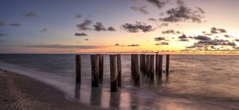 Dilapidated ruins of a pier on Port Royal Beach at sunset. In Naples, Florida stock photography