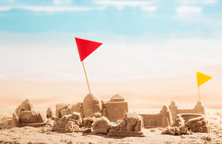Dilapidated sand castles, towers and flags Coliseum on background sea. Royalty Free Stock Photography