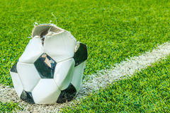 Dilapidated soccer ball in the artificial turf. Royalty Free Stock Images