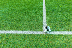 Dilapidated soccer ball in the artificial turf. Stock Photo