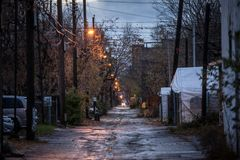 Dilapidated typical north American residential street in autumn in Montreal, Quebec, during a rainy evening with cars parked royalty free stock photo