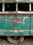 Dilapidated Vintage Green Bus in Burma - Side View with Tire. Window glass has gone missing and the tire has gone flat from neglect over the years Stock Photography