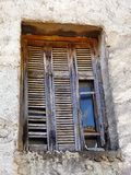 Dilapidated Wooden Window Shutters. Broken and dilapidated wooden window shutters on old Greek village house, Greece Royalty Free Stock Photos