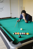Dilemma. The pool player needs the black but it's a difficult shot.  He needs to think through the situation.  The striped balls are blocking his path Royalty Free Stock Photos