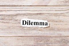 DILEMMA av ordet på papper Begrepp Ord av SAMMANSLUTNINGEN på en träbakgrund Royaltyfri Bild