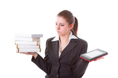 Dilemma between book and ebook reader. Woman having dilemma between stack of books and ebook reader Stock Photography