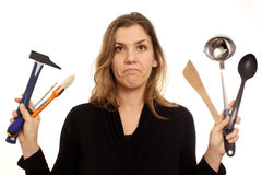 Dilemma, woman hesitating between tools or kitchen Stock Photos