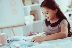 Close up of pleasant girl doing homework royalty free stock image