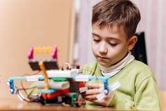 Diligent boy dressed in green sweater sits at the desk with computer and makes the robot from the robotic constructor in stock image