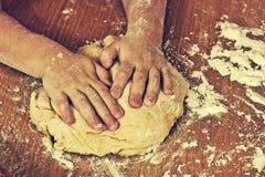Diligent children hands make a dough. Stock Photography