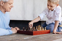 Diligent enterprising boy making a strategic move. Informal education. Intelligent cute smart kid learning how playing chess while his grandpa watching over him Royalty Free Stock Photo