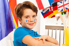 Diligent French schoolboy with flags on cheeks Royalty Free Stock Photo