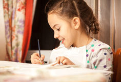 Diligent girl doing drawings with brush Royalty Free Stock Photo