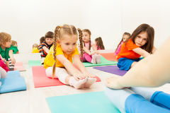 Diligent girl doing stretching exercise on mat royalty free stock photo