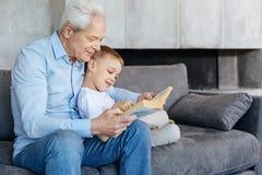 Diligent handsome granddad reading for his grandson Stock Image