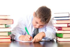 A diligent high school student boy sits in a library with books and learns lessons, writes homework. Exam preparation, testing.  royalty free stock photography