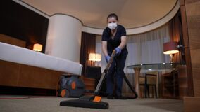 Diligent housemaid vacuuming carpet in hotel room