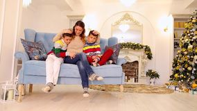 Diligent mother of two twin boys and children sit side by side and in family way embrace on blue sofa in festive. Affectionate mother and successful woman shows stock video