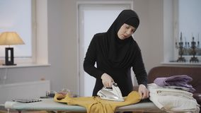 Diligent Muslim housewife in black hijab ironing yellow sweater at home. Young beautiful woman doing housework. Eastern