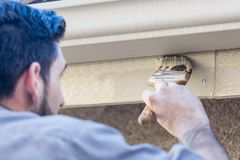 Diligent Professional Painter Using Brush to Paint House Fascia Under Rai Royalty Free Stock Image