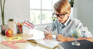 Male pupil reading english book. Diligent schoolboy in eyeglasses reading english textbook, pointing finger, preparing homework stock video footage