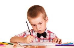 Diligent schoolboy sitting at table, paints in album . Stock Photos