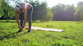 Diligent senior woman doing stretching exercises in the park stock video footage