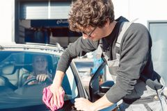 Diligent service man helping woman cleaning her car in commercial wash. Diligent service men helping women cleaning her car in commercial wash with cloth royalty free stock images