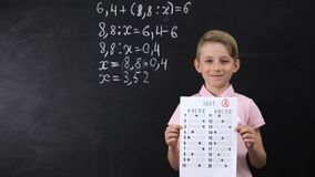 Diligent smiling schoolboy showing excellent test, math exercise written behind. Stock footage stock video