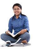 Diligent student on floor. A female student sitting on the floor while holding the book Royalty Free Stock Photo