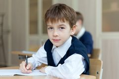 Diligent student sitting at desk, classroom Stock Photos