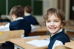 Diligent student sitting at desk, classroom Stock Images