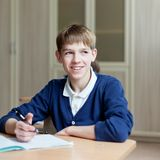 Diligent student sitting at desk, classroom Stock Photography
