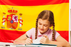 Diligent teenage student learning Spanish at class. Diligent teenage student, Caucasian girl, writing with a pen in her copybook, Spanish flag behind Royalty Free Stock Photography