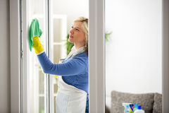 Diligent woman cleans window Royalty Free Stock Photo