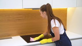 Caucasian girl in blue equipment cleaning plate in kitchen