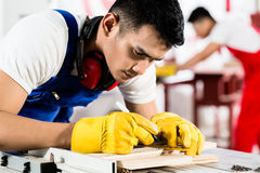 Diligent worker in factory working on wood. In the background his colleague is cutting a piece Royalty Free Stock Photography