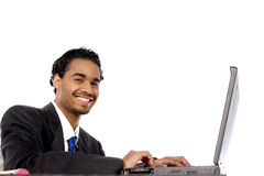 Diligent young man. Smiling as he works on his computer Royalty Free Stock Image