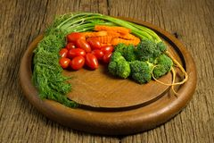 dill. baby tomatoes. carrot. broccoli. on old chopping borad woo Royalty Free Stock Photos