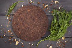 Dill bunch with round cork board on wood background. W. Dill bunch with round cork board on wood background. Top view with copy space Stock Images